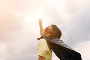 Young boy wearing a cape with arm raised towards sky