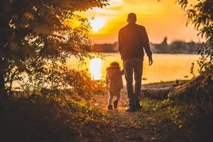Parent and child taking unset stroll along lake
