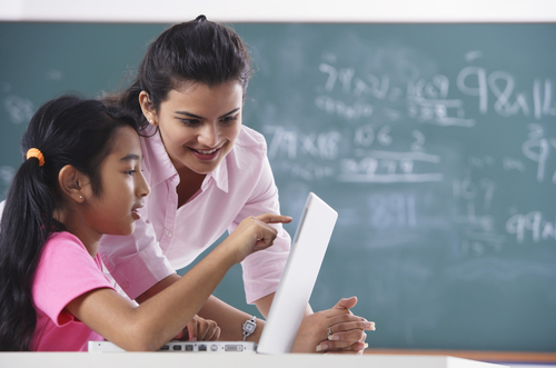 Photo of a female instructor and a student pointing to the screen on a laptop and a green chalkboard with writing in the background