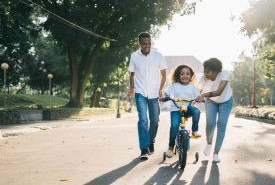 Parents helping their daughter ride a bicycle