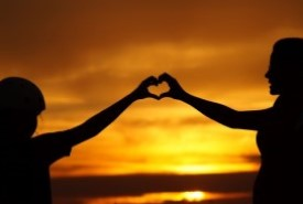Two people forming the shape of a heart with their hands