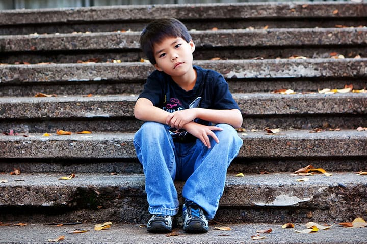 a young boy sitting on steps