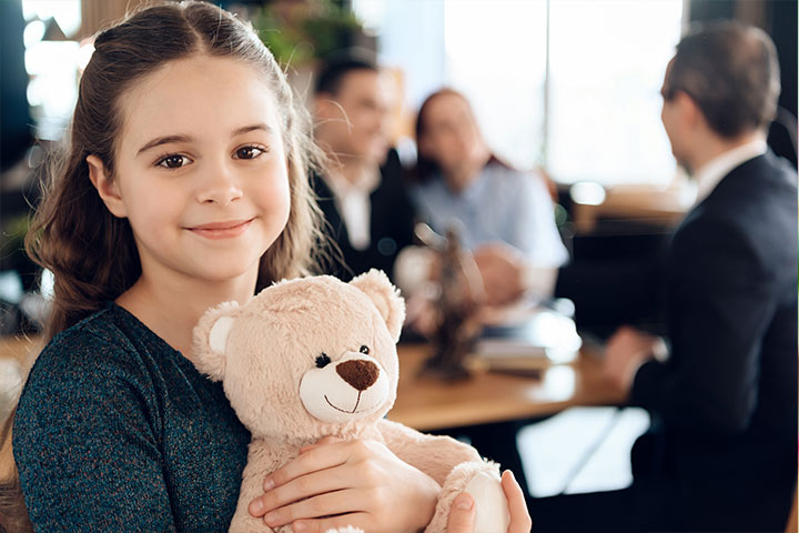 a young girl smiling holding a teddy bear